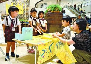 レジ袋の購入を呼び掛ける園児(左の3人)=徳島市のイオンモール徳島