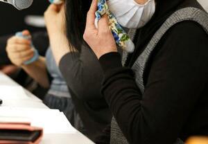 記者会見で涙を拭う、殺害された女性の母親(手前)=20日午前、福岡市