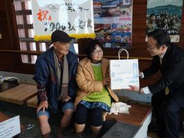 1万人目の利用者となり、記念品を受け取る島さん(中)=鳴門駅前の足湯施設