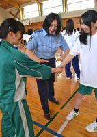 女性警察官(中)に教わりながら、護身術の練習をする女子生徒=阿南市の富岡東高羽ノ浦校