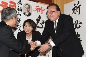 当選確実の知らせが届き、支援者と握手する福山氏=22日、徳島市八万町の選挙事務所