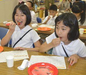 3種類のトマトを食べ比べる児童=徳島市南島田町3のキョーエイタクト店