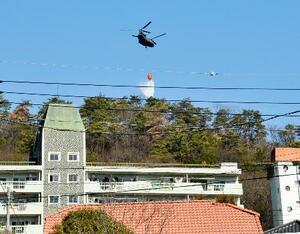 栃木県足利市の山林火災現場で消火活動に当たるヘリコプター=2月28日午前