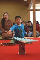 真剣な表情で扇子を投げる参加者=徳島市の徳島城博物館