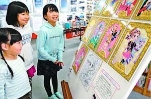 愛らしいイラストに見入る子ども=牟岐町立図書館