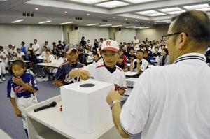 こども野球のつどいの組み合わせ抽選会で、くじを引く選手ら=徳島市の新聞放送会館
