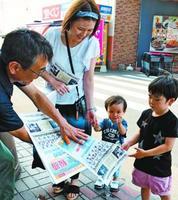 鳴門高校の甲子園出場決定を伝える速報を受け取る買い物客(右の3人)=鳴門市撫養町
