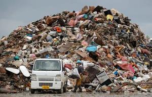 豪雨で水に漬かった家財などが捨てられ、積み上げられたごみの山=11日午後3時44分、熊本県人吉市