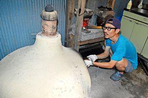 自作の窯でコーヒー豆を焙煎する寺内さん=牟岐町の出羽島