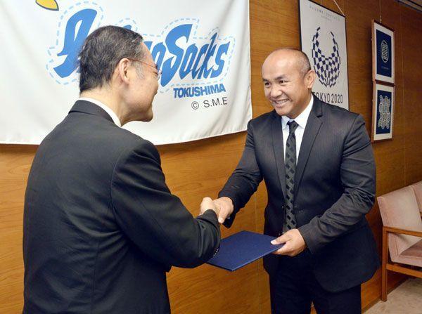 委嘱状を受け取り、飯泉知事(左)と握手する張氏=県庁