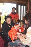 えびすの木偶で手をなで、福を呼び込む中内会長(左)=阿南市吉井町