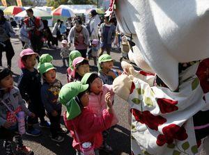 狸のゆるキャラ「鹿の子姫」と触れ合う子どもたち=徳島市の藍場浜公園