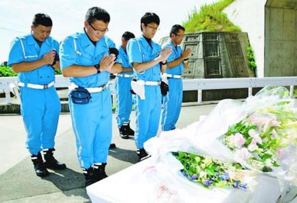 献花台の前で犠牲者の冥福を祈る県警高速隊員=鳴門市大津町大幸