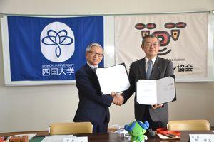 協定書を交わす松重学長(左)と谷会長=四国大