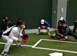 捕手の構え方について教える里崎さん(左端)=阿南市桑野町の県南部健康運動公園
