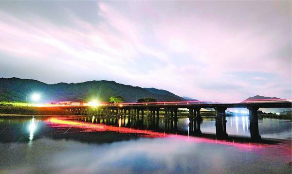 勝浦川に架かる星谷橋を夜間に長時間露光で撮影。雲が流れる夜空に橋が浮かび上がった=勝浦町星谷