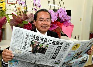 自身の当選を報じる新聞に目を通す遠藤さん=午前8時ごろ、徳島市北島田町1の事務所
