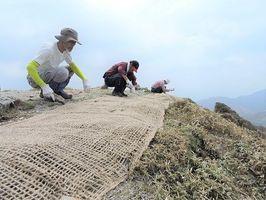 登山道周辺の山腹にネットを張る三嶺の自然を守る会の会員(県提供)=剣山