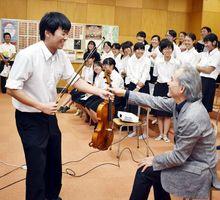 調整した弦楽器を徳島市立高校生に渡す松下さん=同校