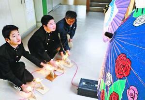 和傘をライトアップする照明を調整する生徒ら=つるぎ高