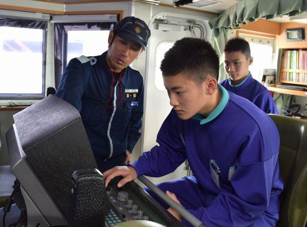 海上保安官から巡視船のレーダーの見方を教わる高田さん(中央)=小松島市の徳島小松島港