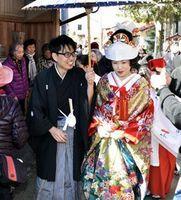 住民らに見守られながら、古民家が軒を連ねる通りを歩く福山さん夫妻=牟岐町沖の出羽島