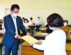 鈴田保健福祉部長(右)に抗議文を提出する事業者の関係者=徳島市役所