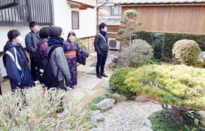 福本さん(右から2人目)の案内で庭を観賞する参加者=美馬市脇町のうだつの町並み