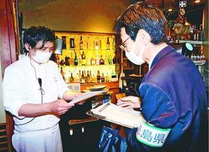 飲食店で時短への協力を呼び掛ける県職員(右端)=徳島市富田町2
