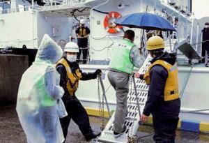 愛媛県伊方町の三崎港で巡視船に乗り込む住民=22日午前10時59分