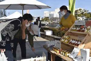 商品の説明をする出店者と買い物客=2020年12月27日、徳島市のしんまちボードウオーク