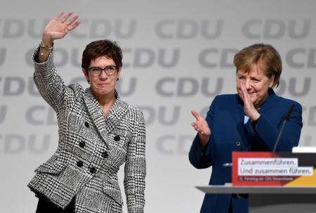 7日、ドイツ北部ハンブルクでのキリスト教民主同盟の党大会で、メルケル首相(右)の後任党首に選ばれ手を振るクランプカレンバウアー氏(ロイター=共同)
