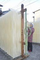 天日干ししたそうめんに箸を通す製麺業者=つるぎ町半田の赤川製麺