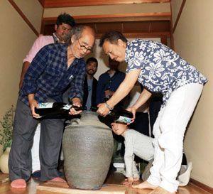 古酒を造るため、かめに泡盛を注ぐ島袋顧問(左)と佐藤代表取締役=阿南市吉井町