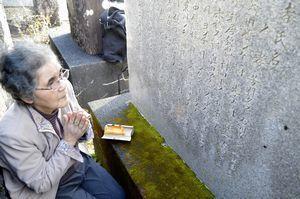 「昭和南海地震震災碑」に刻まれた母親と叔母の名前に向かい、両手を合わせる天野さん=21日午前9時40分、牟岐町中村