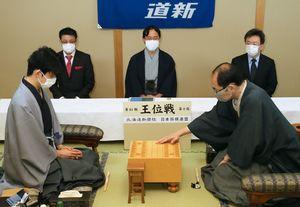 第61期王位戦第2局で初手を指す木村一基王位。左は藤井聡太七段=札幌市