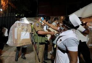 スリランカ議会選で投票締め切り後、投票箱を運ぶ選挙管理人ら=5日、コロンボ(ロイター=共同)