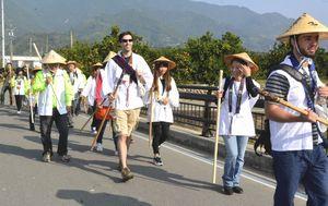 橋の上は杖を突かないという注意を守り、歩く遍路体験の外国人=勝浦町生名