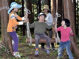 森林の中でブランコを楽しむ子どもら=神山町神領の大粟山