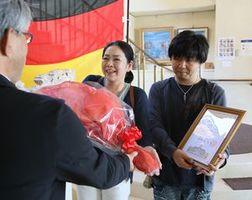 100万人目の入館者として森館長(左)から認定証と花束を受け取る松村夫妻=鳴門市大麻町の市ドイツ館