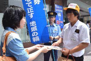 通行人に少年非行防止を呼び掛けるチラシなどを配る八万中の生徒(右)=徳島駅前
