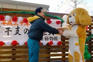 犬の着ぐるみに鏡餅を手渡す近久園長(左)=徳島市のとくしま動物園