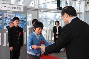 飯泉知事(右)から賞状を受け取る入賞者=鳴門市鳴門町の観光遊歩道「渦の道」