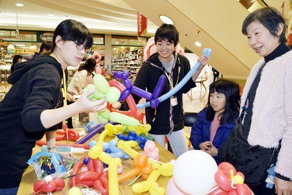 色とりどりのバルーンアートを見て楽しむ家族連れ=徳島市のアミコ専門店街