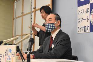 クラスターの発生を受け県の対応などを説明する飯泉知事(右)=県庁