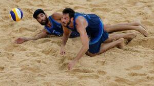 ビーチバレー男子1回戦、ポーランド組との対戦でレシーブに跳ぶイタリアのペア=2日、潮風公園(ロイター=共同)