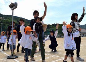 手を挙げて保護者と一緒に横断歩道を渡る練習をする園児=つるぎ町の半田小学校