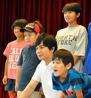 愛媛県西予市の避難所を訪れ、子どもたちと写真撮影に応じる「嵐」の松本潤さん=21日午前