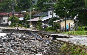 大雨による増水で削られた道路=10日午前9時、岐阜県高山市