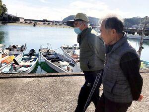 牟岐港を歩く竹本さん(右)と中磯さん。昭和南海地震から75年がたち、港の風景も当時から大きく変わった=牟岐町牟岐浦